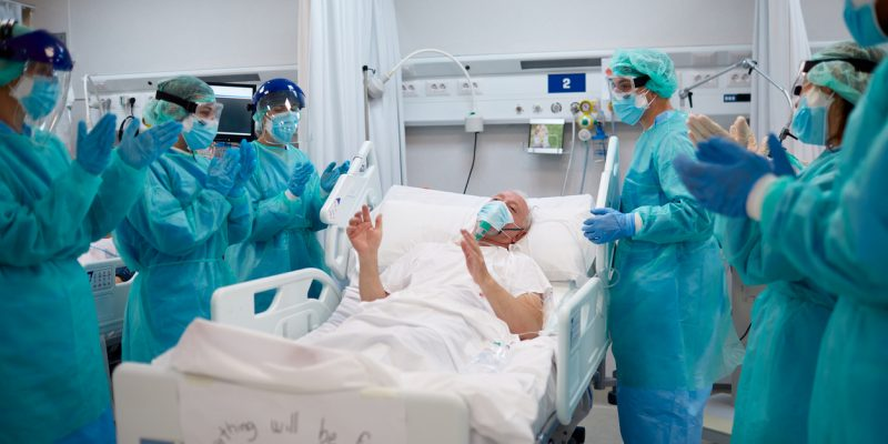 Healthcare workers are clapping at a recovered patient.